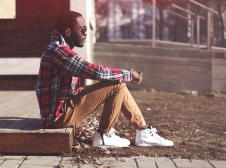 Lifestyle fashion portrait of stylish young african man listens to music evening and enjoys sunset, wearing a hipster plaid red shirt and sunglasses sitting in profile outdoors